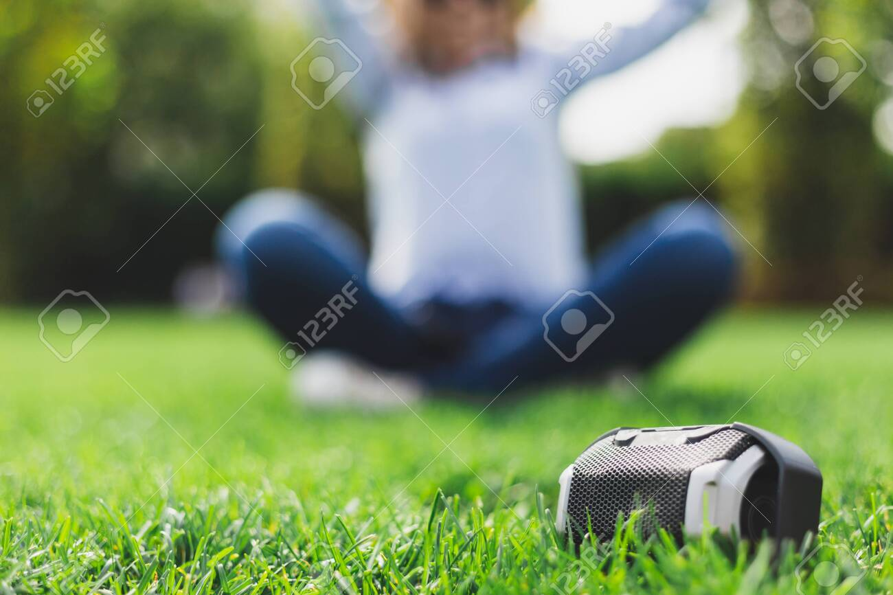 Portable speaker next to a girl relaxing in the lotus position - Office woman in shirt doing some yoga in nature with a wireless loudspeaker in front of her - 150340822