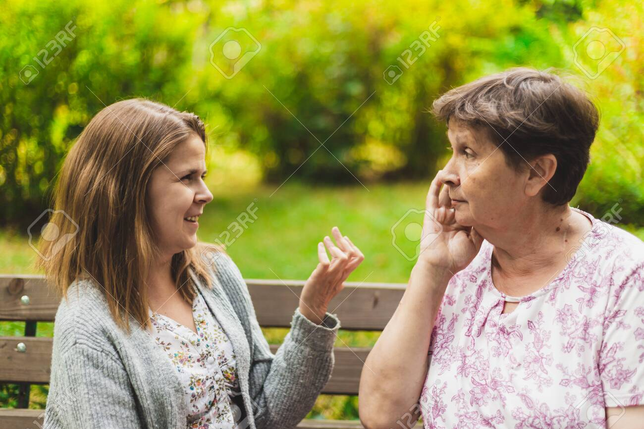 Mother and daughter talking on a bench - Teen giving advice to an adorable old woman - Two women chatting outside - 150499804