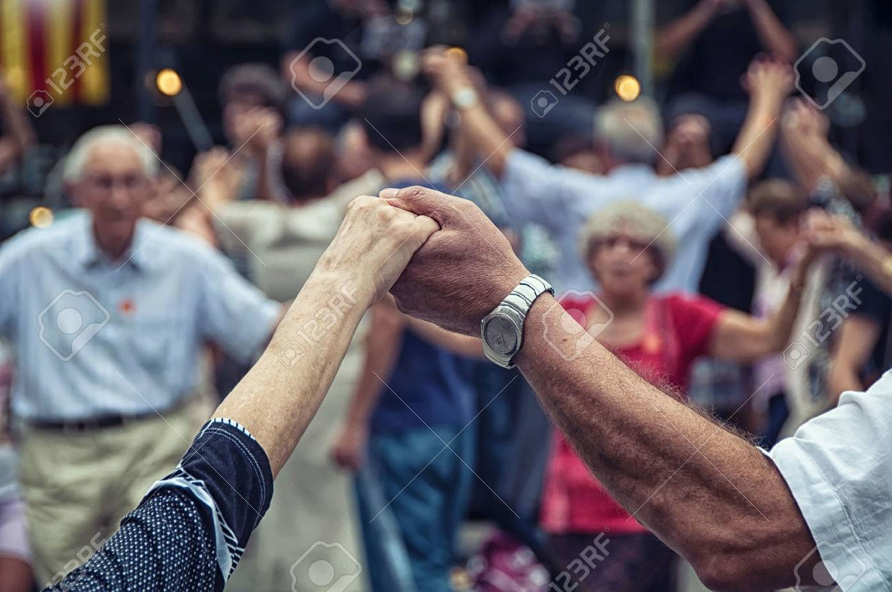View of senior people holding hands and dancing national dance Sardana at Plaza Nova, Barcelona, Spain. It is a type of circle dance typical of Catalonia - 38918983