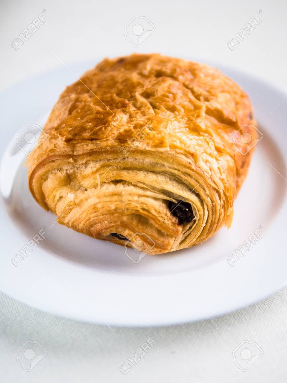 Vertical View Of A Single French Chocolate Croissant On A White