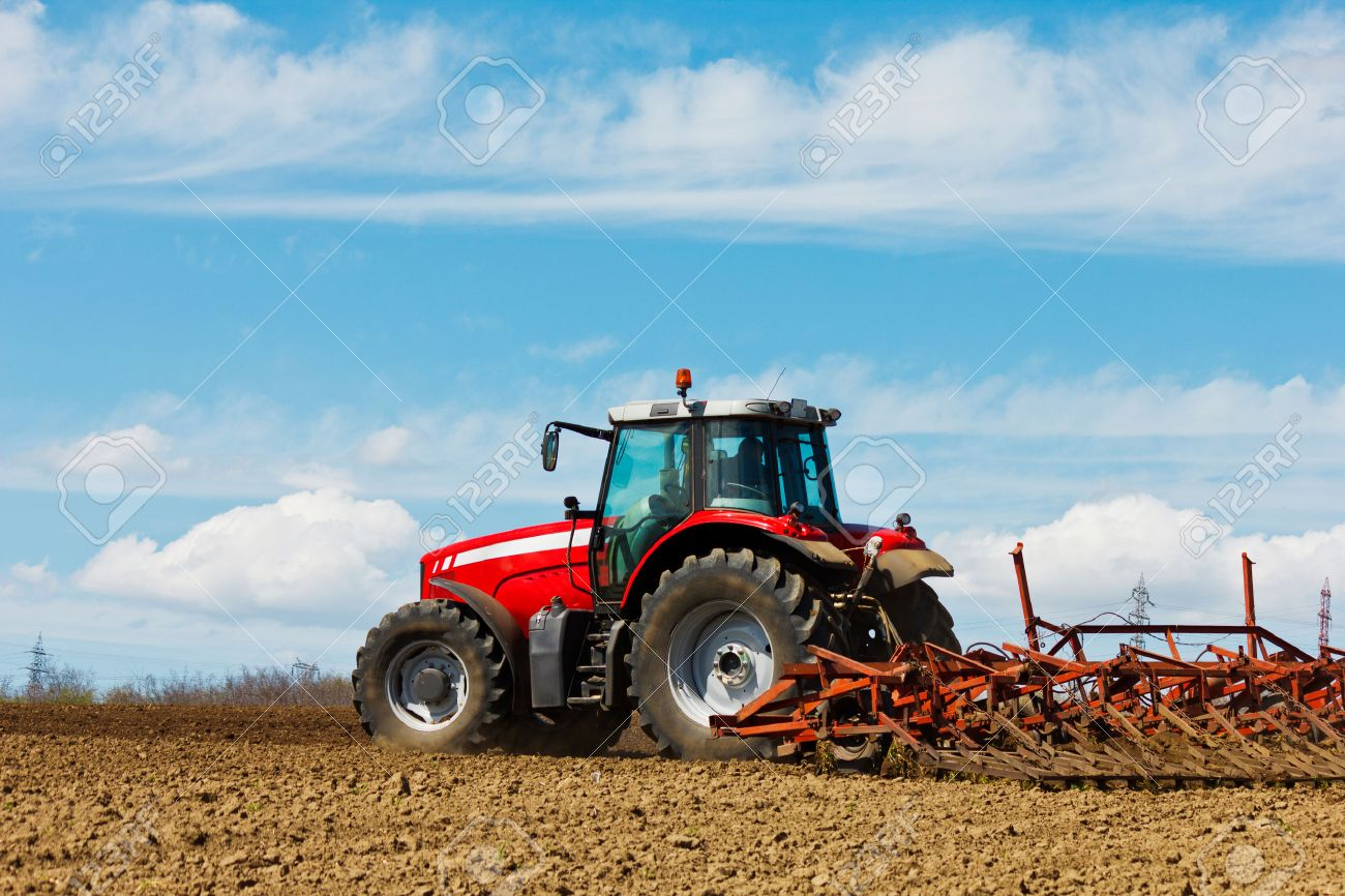 Farmer plowing the field Cultivating tractor in the field Red farm tractor with a plow in a farm field Tractor and Plow - 30452624