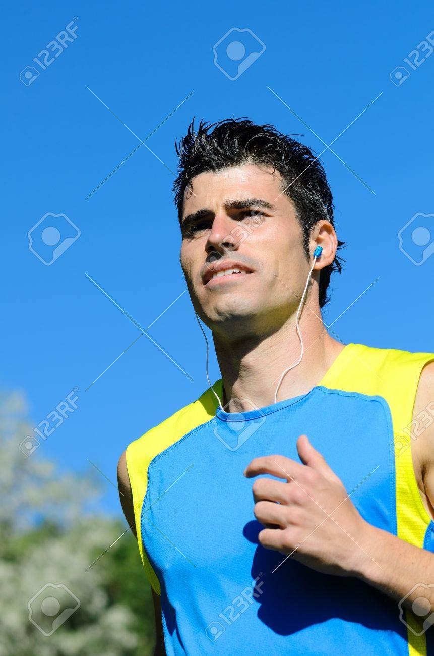Handsome man running in park with earphones. Stock Photo - 14301031