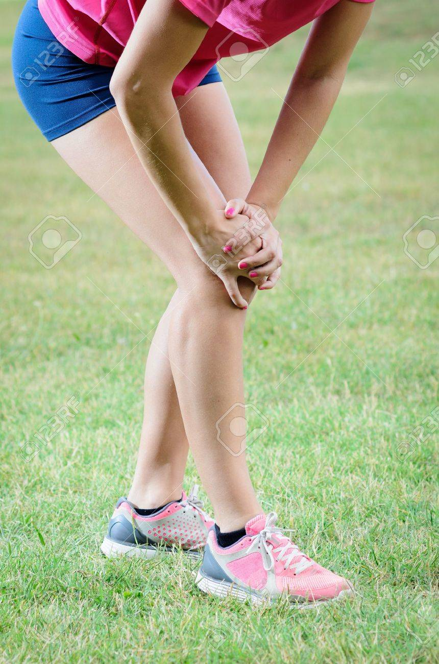 Female athlete suffer because an injury in her knee Stock Photo - 14332184