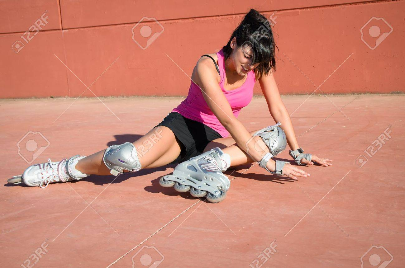 Female roller skater accident over hard asphalt  She wears protections and sport wear and shows face of suffering Stock Photo - 14888240