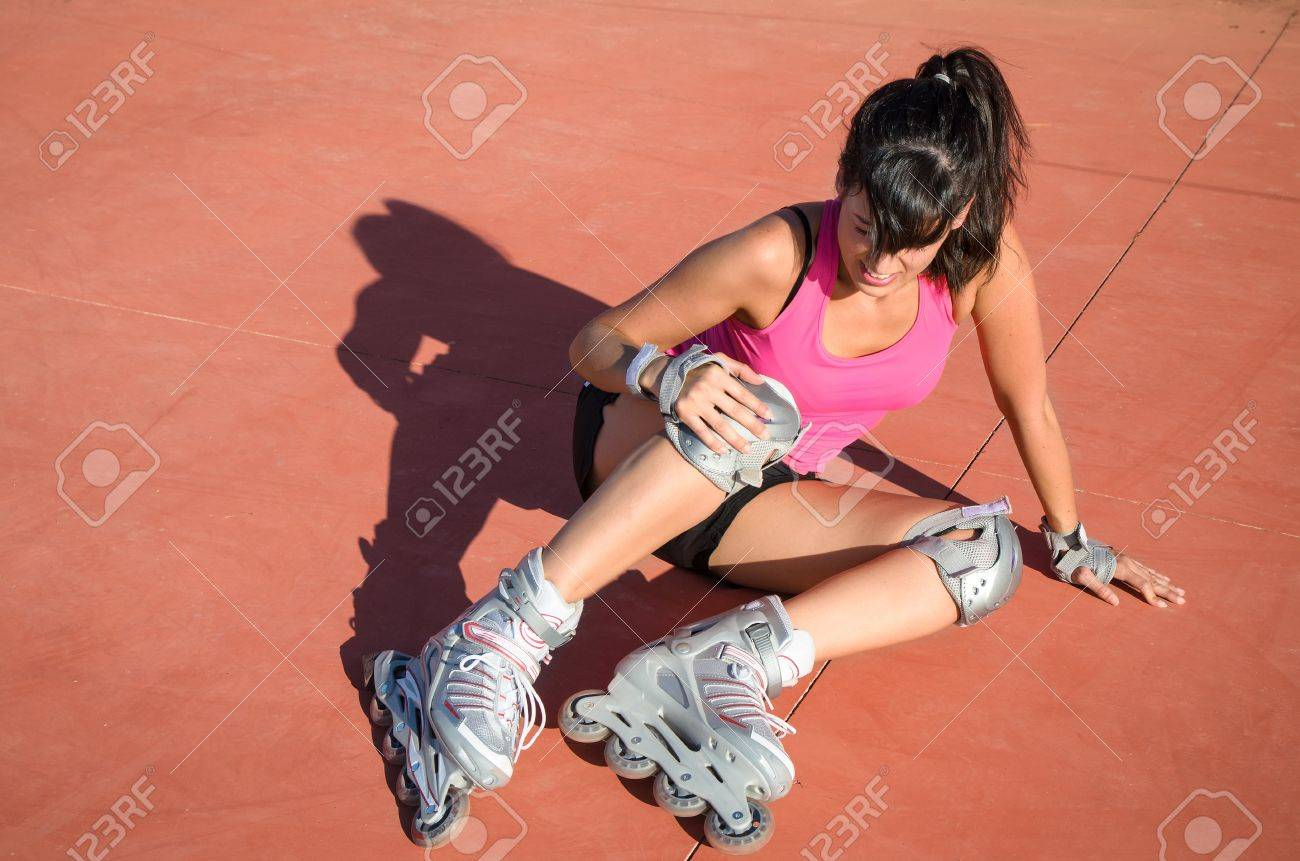 Female roller skater with protections falls by accident. She suffer an injury, grabs her knee and shows face of pain. Stock Photo - 14889961