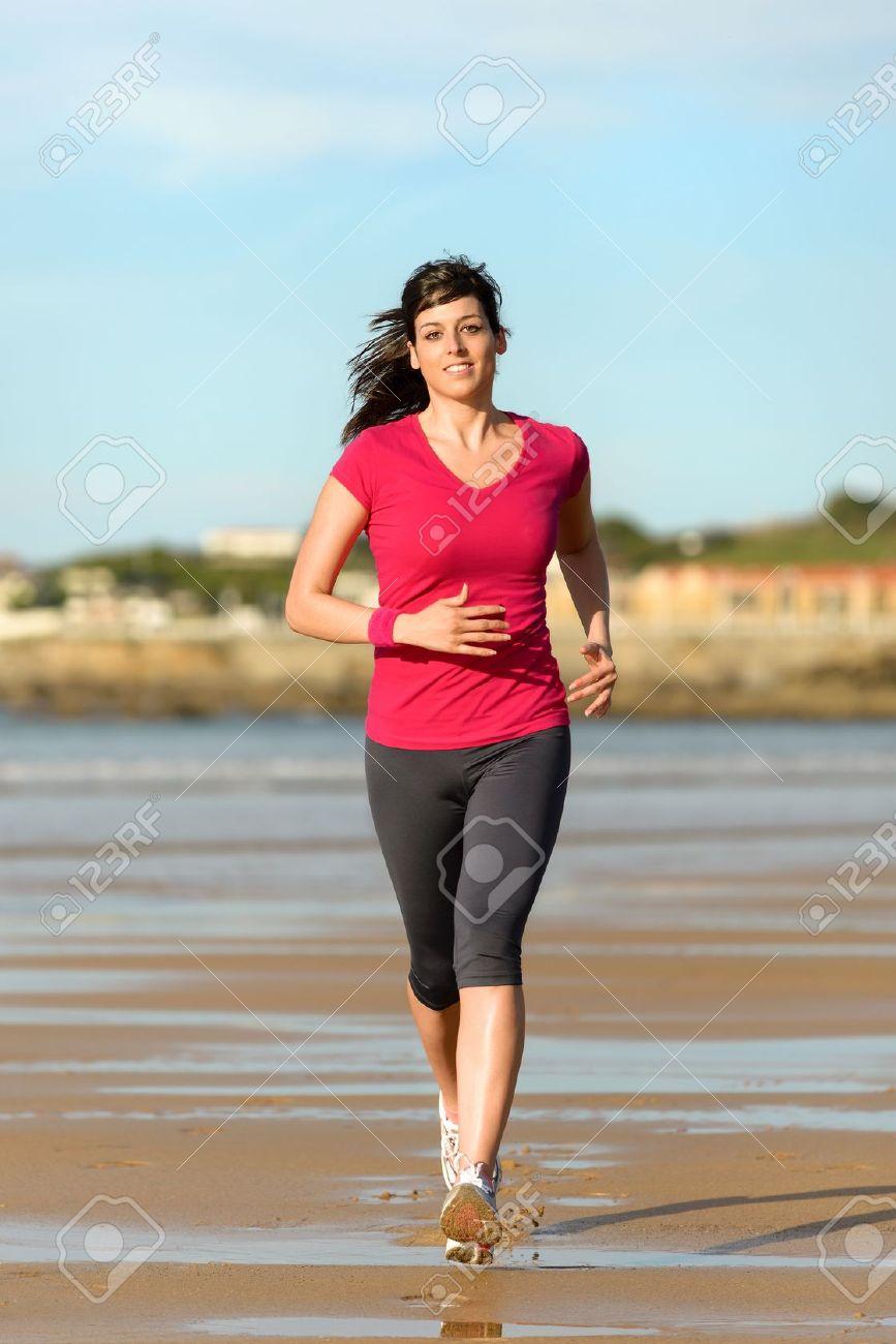 Woman running on beach at sunset. Beautiful fitness caucasian girl exercising outdoors on sea background.  Playa de San Lorenzo, Gijon, Spain. Stock Photo - 18658071