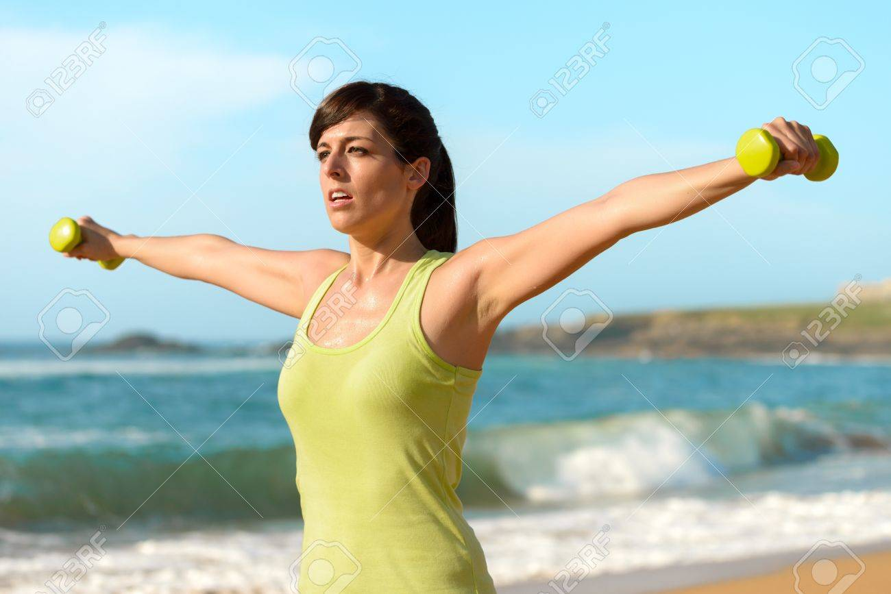 w training shoulders dumbbells on beach summer work stock photo w training shoulders dumbbells on beach summer work out fitness and exercising weights outdoor caucasian sport girl training