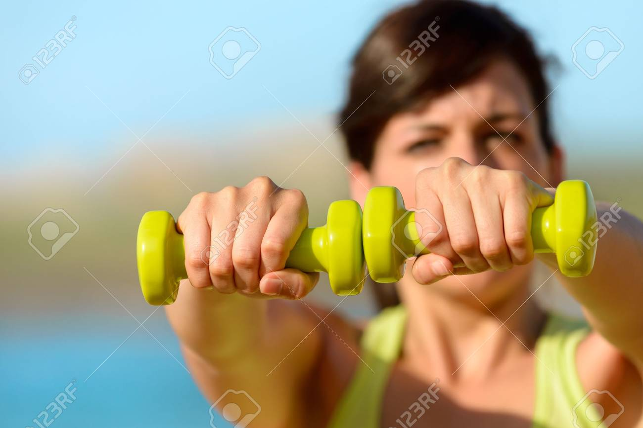 Woman training  shoulders with dumbbells on beach. Summer work out, fitness and exercising with weights outdoor. Caucasian sport girl training hard. Copy space. Stock Photo - 19458935