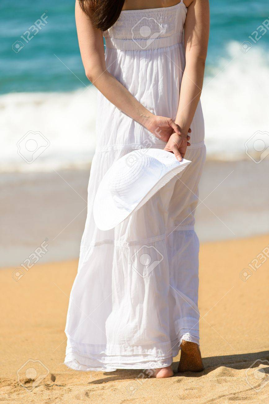 dc50c440ed9d Stock Photo - Woman in white dress walking on beach towards the sea.  Vacation and leisure on coast in summer.
