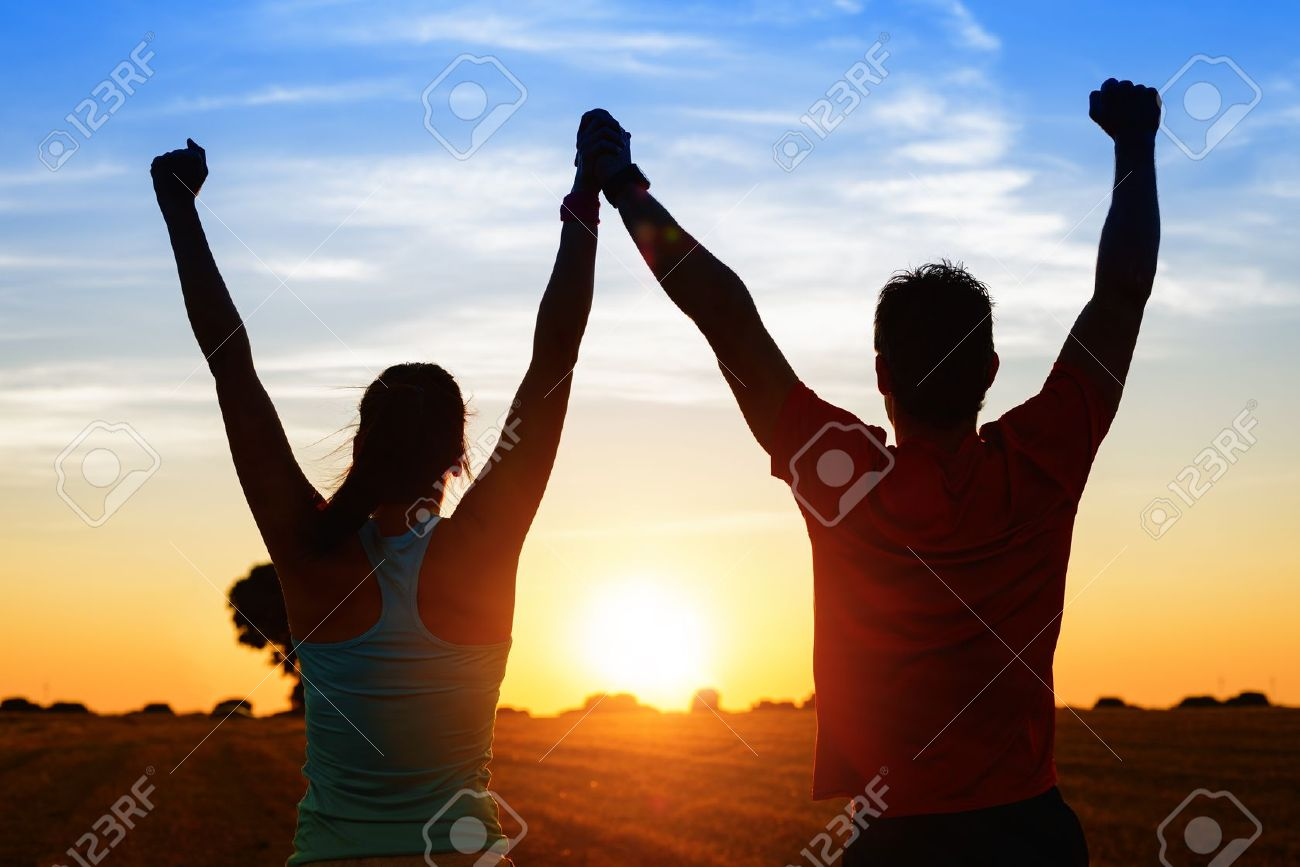 Successful couple of young athletes raising arms to golden summer sunset sky after training Fitness man and woman with arms up celebrating sport goals after exercising in countryside field - 21976515