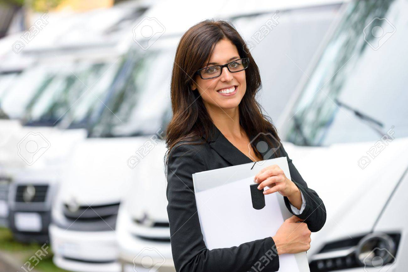 Successful sales business woman in van transport trade fair. Commercial exhibition and rental vehicle concept. Beautiful female seller or salesman holding car keys. Stock Photo - 22139842