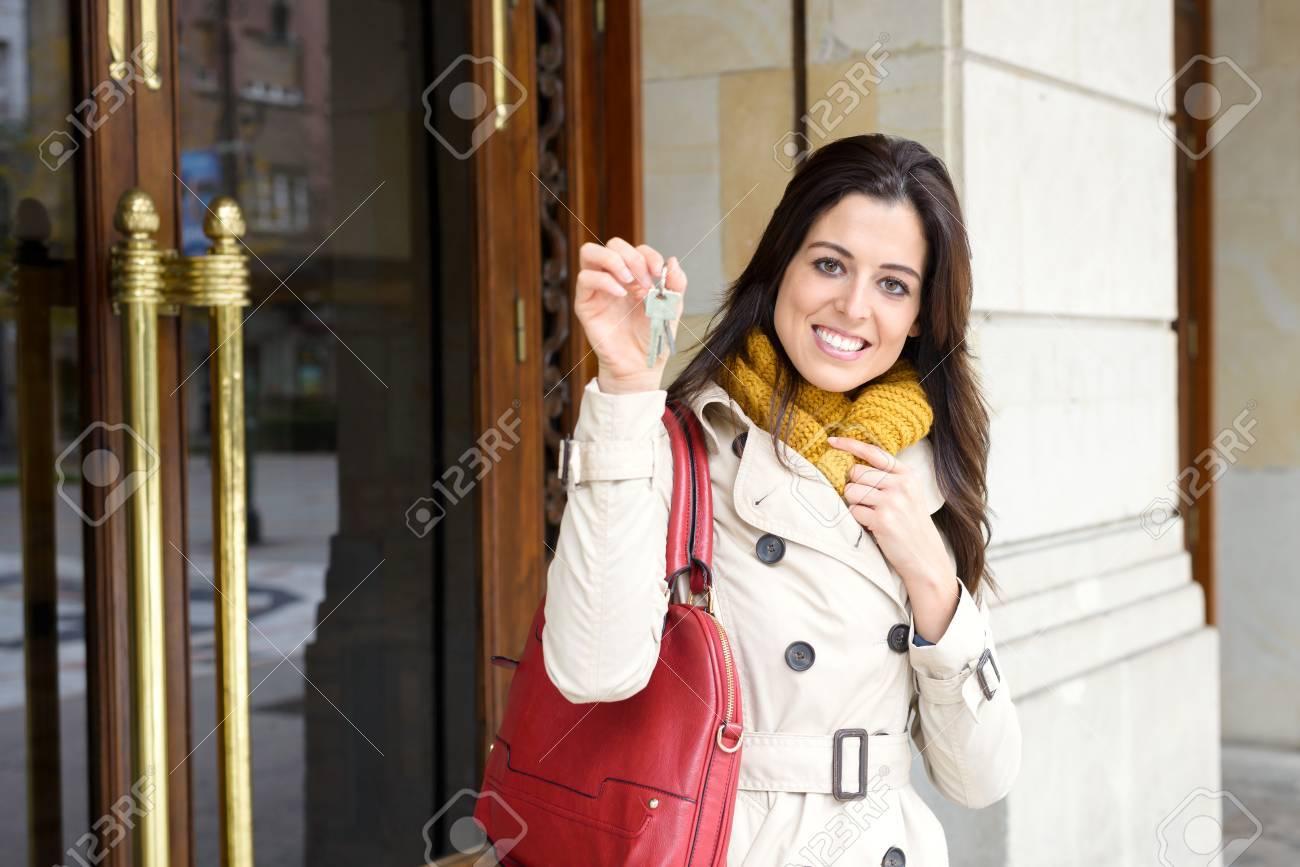 Ingressi Esterno Di Casa : Donna allegra che tiene le chiavi di casa in condominio porta d