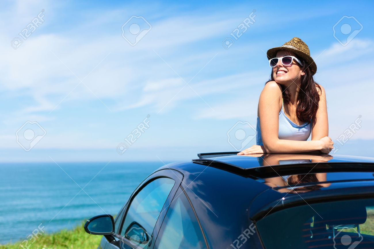 Relaxed happy woman on summer travel vacation to the coast leaning out car sunroof with the sea on background - 27578002
