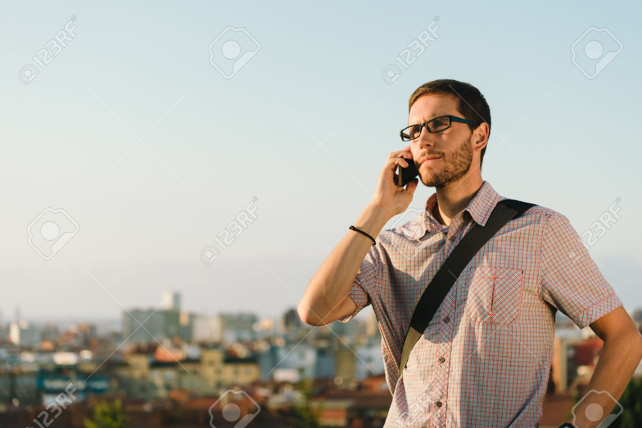 professional casual man during a job call outside against city professional casual man during a job call outside against city background young entrepreneur working outside