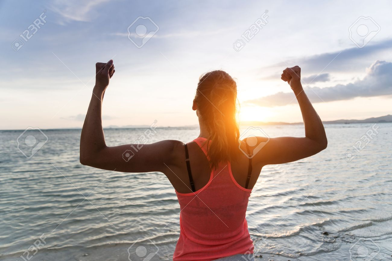 sporty strong w raising arms and enjoying dom and success sporty strong w raising arms and enjoying dom and success towards the sun and sea on