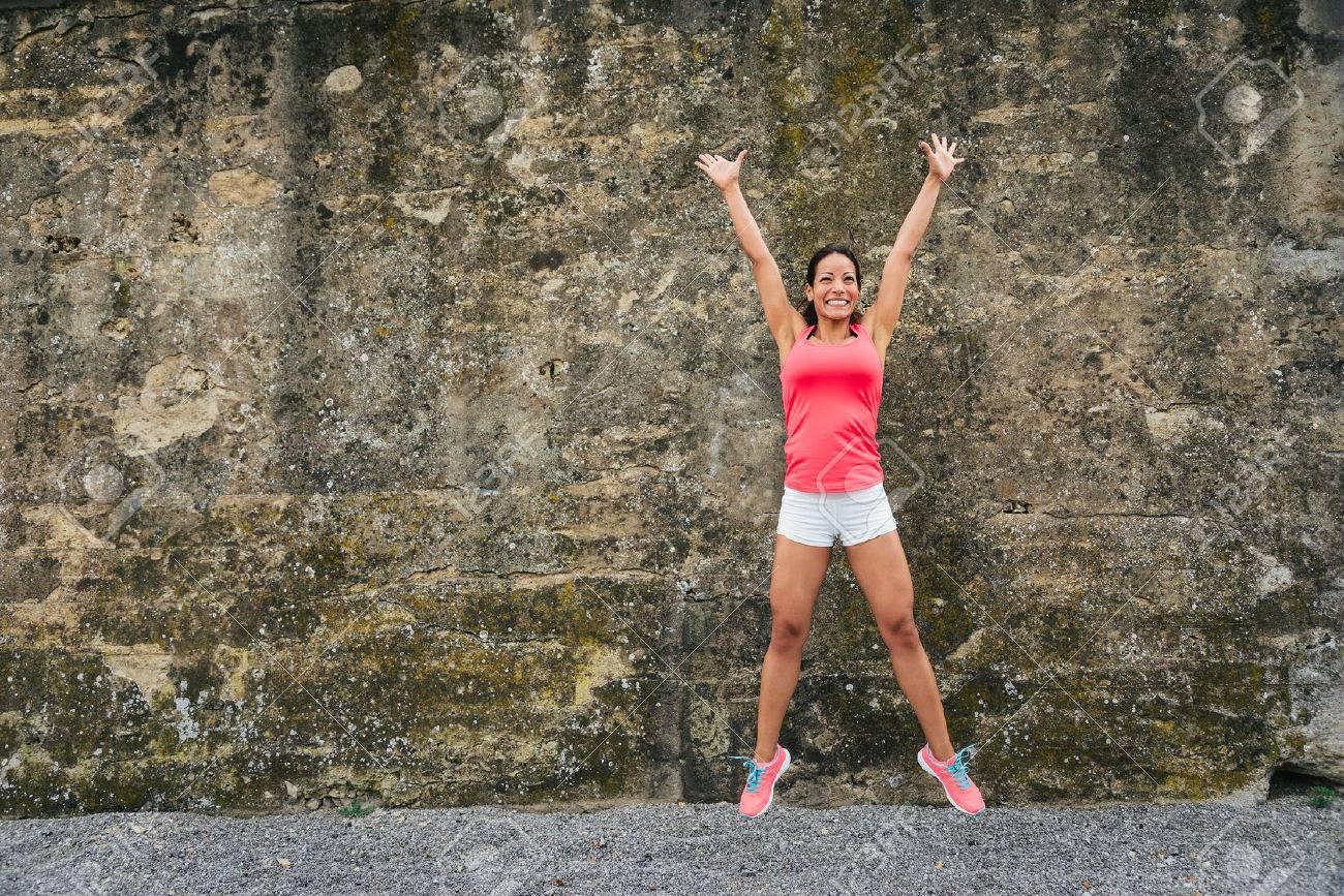 Happy female athlete jumping for celebrating exercising and fitness success. Stock Photo - 43152966