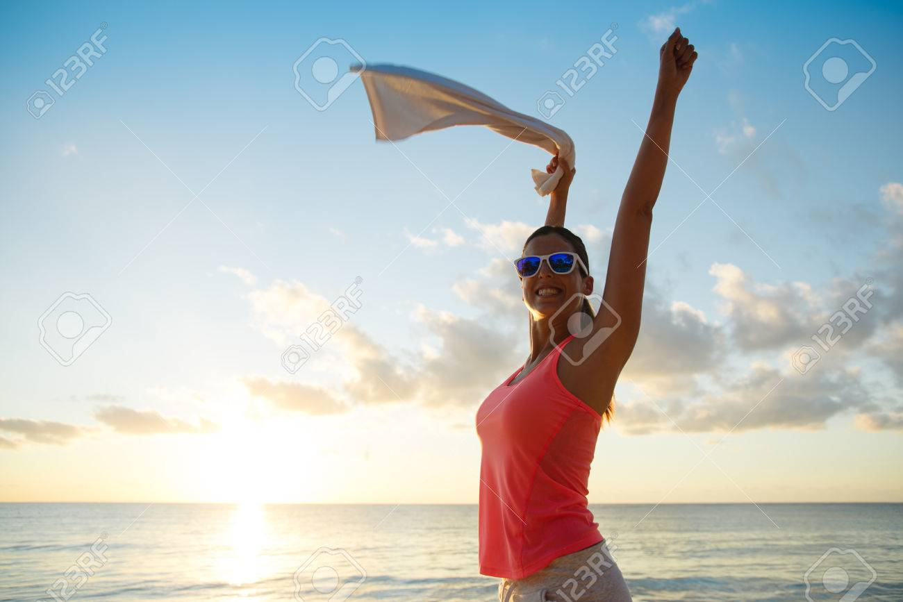 Fitness happy woman celebrating fitness workout success towards the sea and sunset at the beach. Training motivation and healthy lifestyle concept. - 55458520