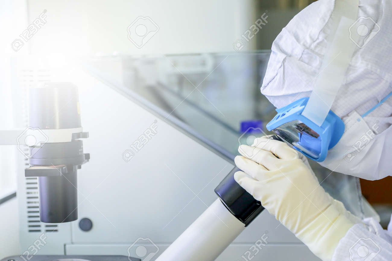 Lab scientists wear protective clothing looking for microscopes while doing medical research in a science laboratory. - 156743727