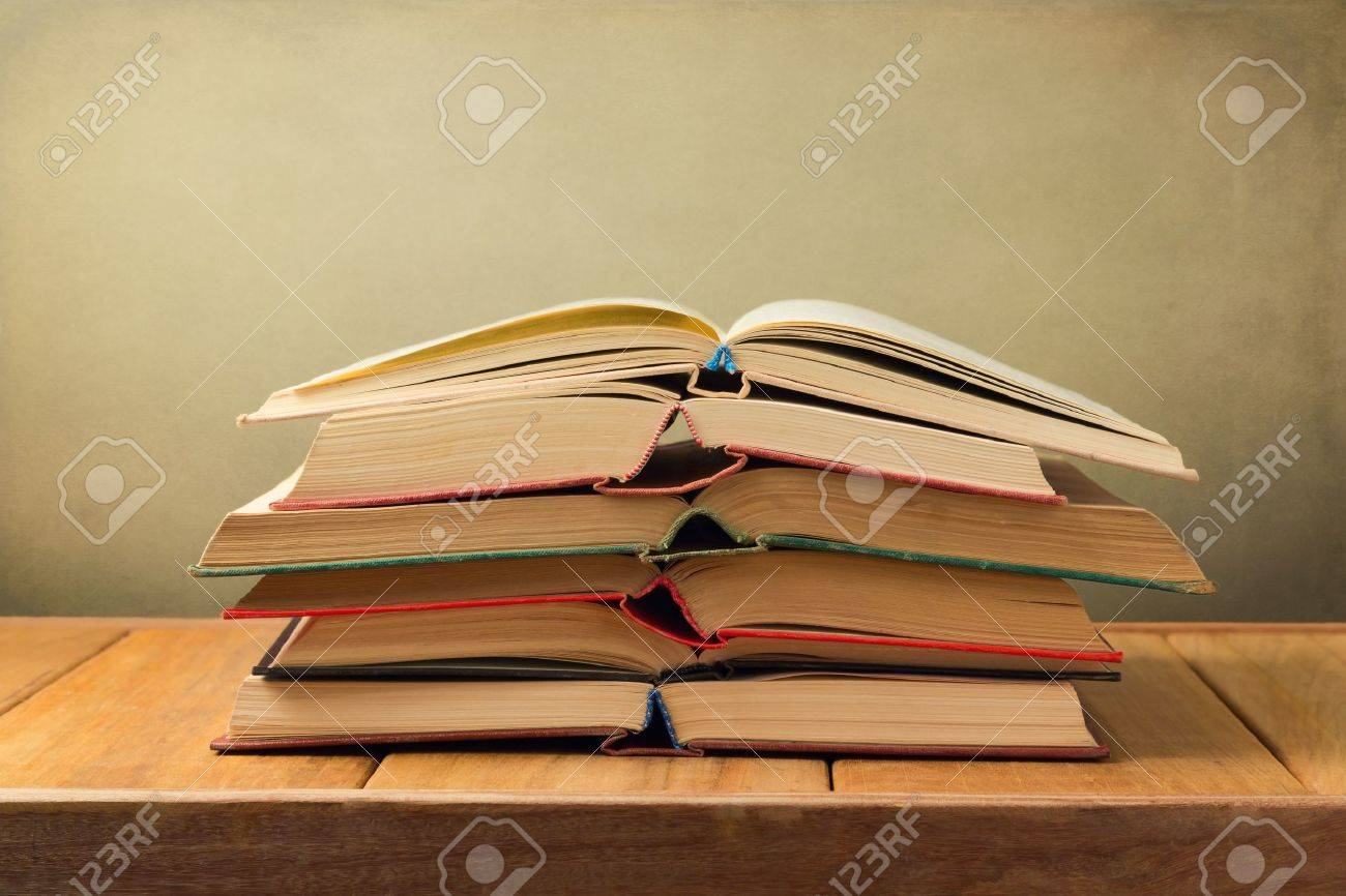Stack of open old books on wooden table over grunge background Stock Photo - 21196321