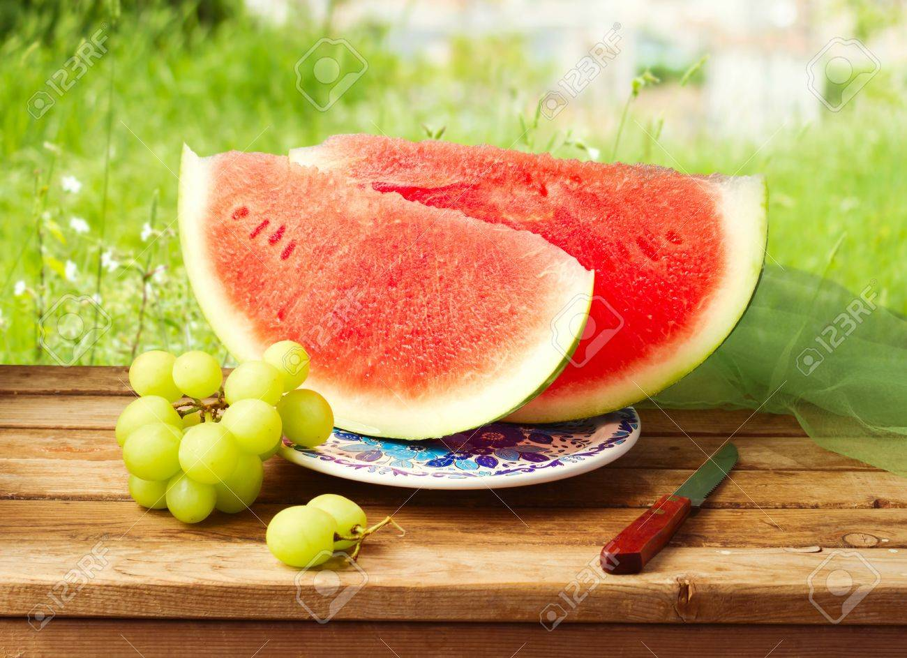 Watermelon and grapes on wooden table over grass bokeh background. Stock Photo - 21184932