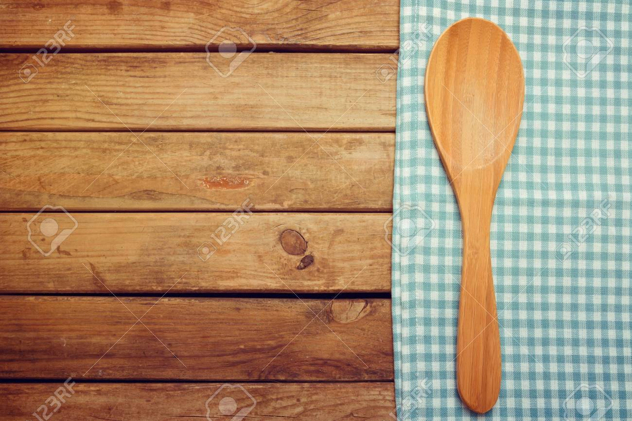 Wooden spoon and tablecloth over wooden background Stock Photo - 21736198