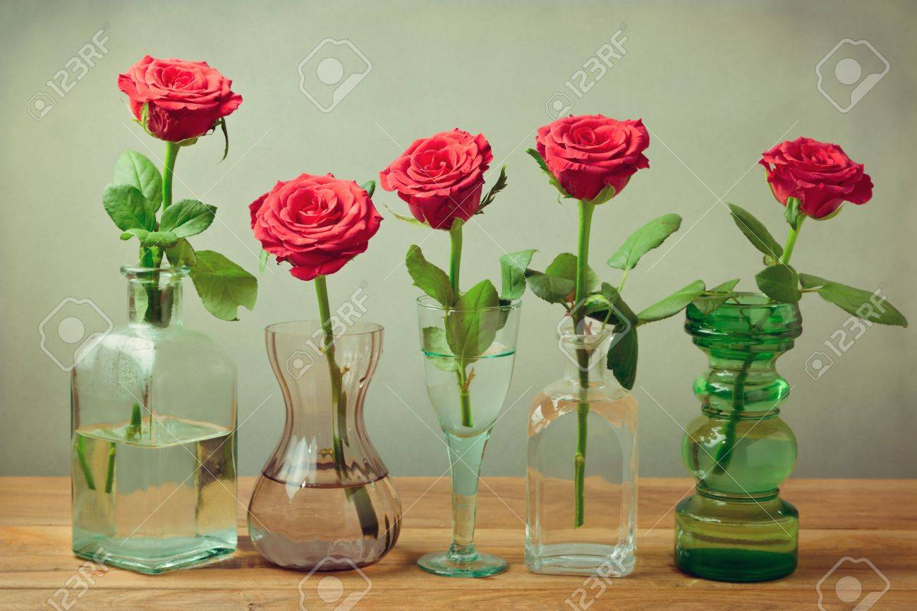 Rose flowers in vases, bottles and glasses  Still life composition Stock Photo - 21716426