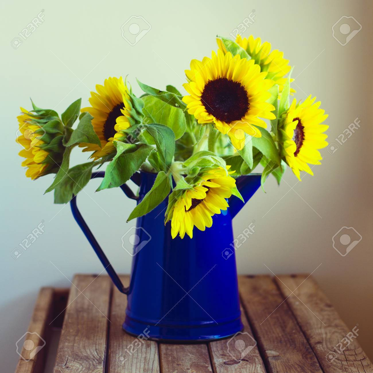 magnifique bouquet de tournesol en émail pichet sur table en bois