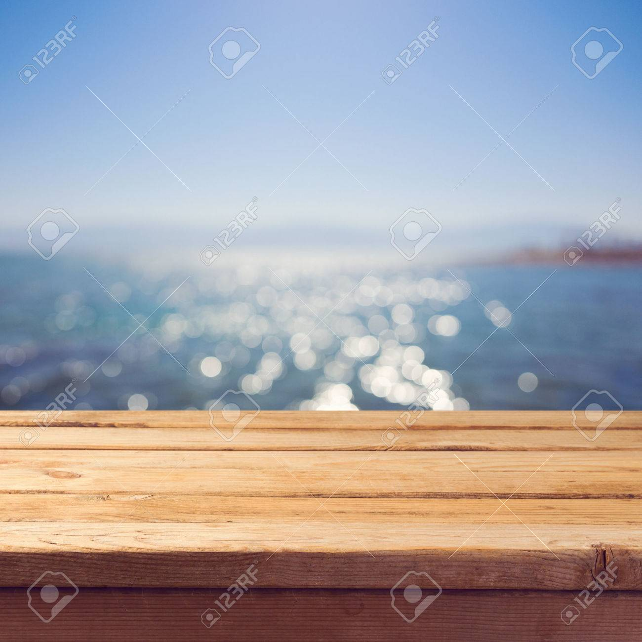 Empty wooden deck table over sea bokeh background  Summer holiday
