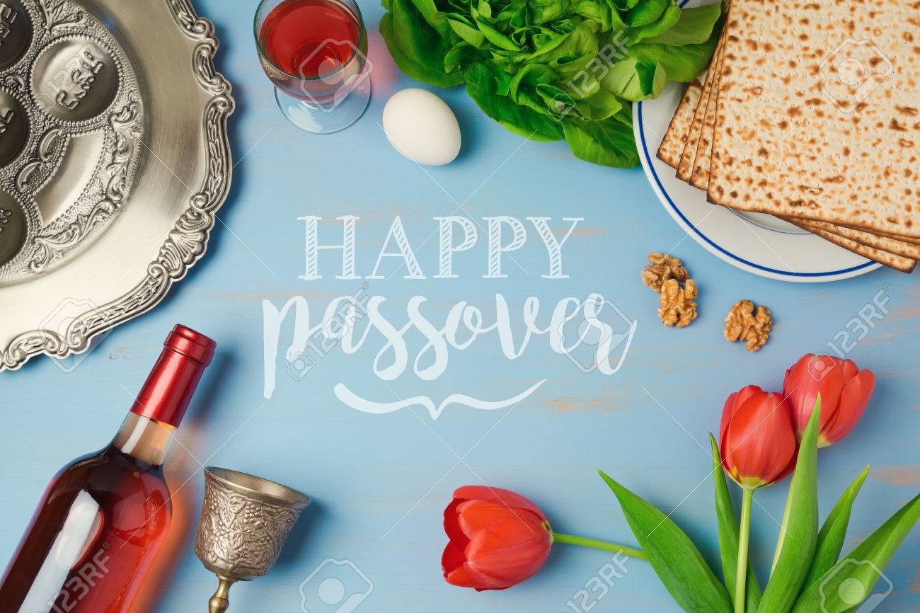 Passover holiday greeting card with seder plate, matzoh, tulip flowers and wine bottle on wooden background. Top view from above - 73346710