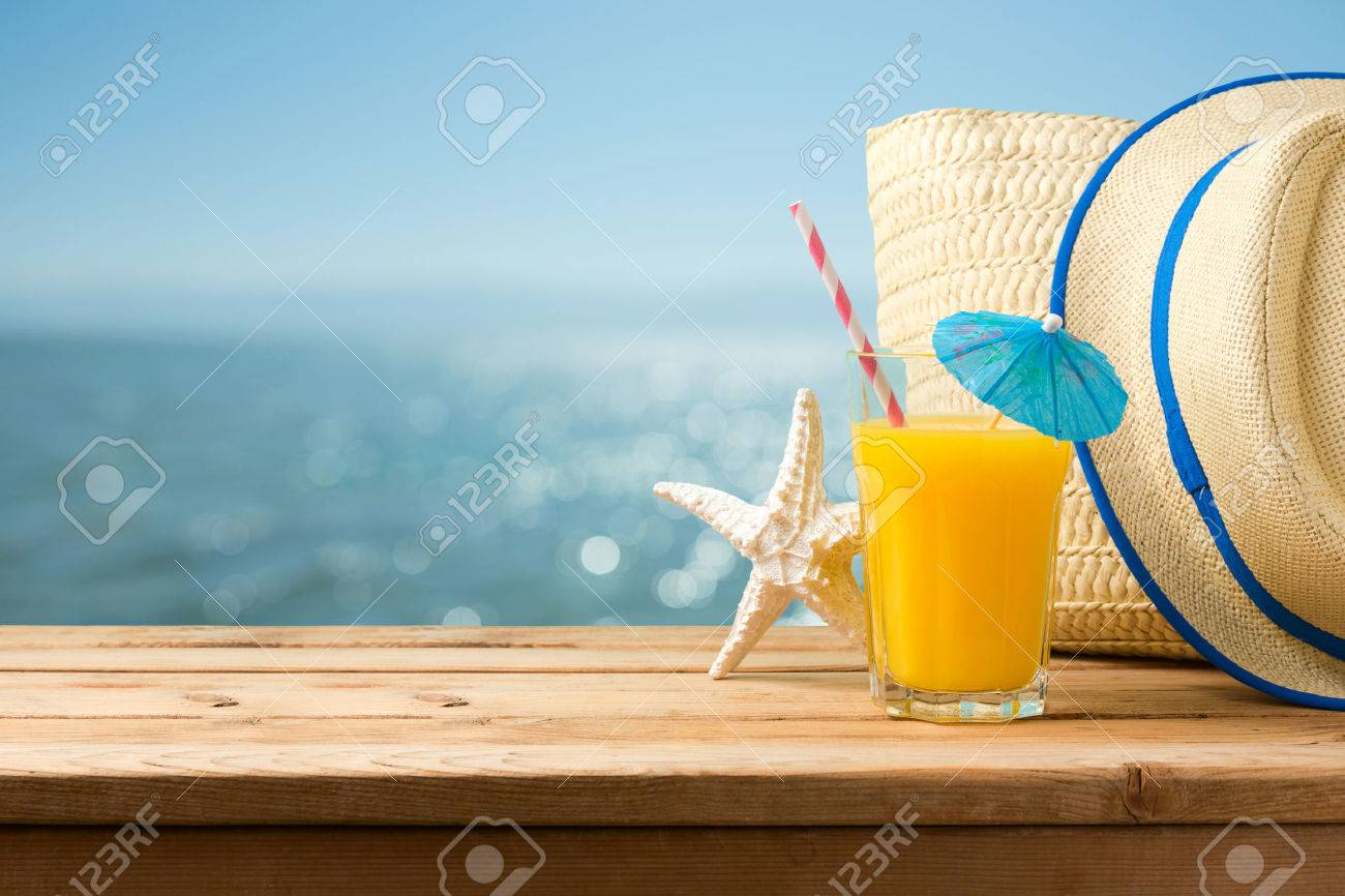 Summer holiday vacation concept with orange juice, hat and bag over sea beach background - 75735356
