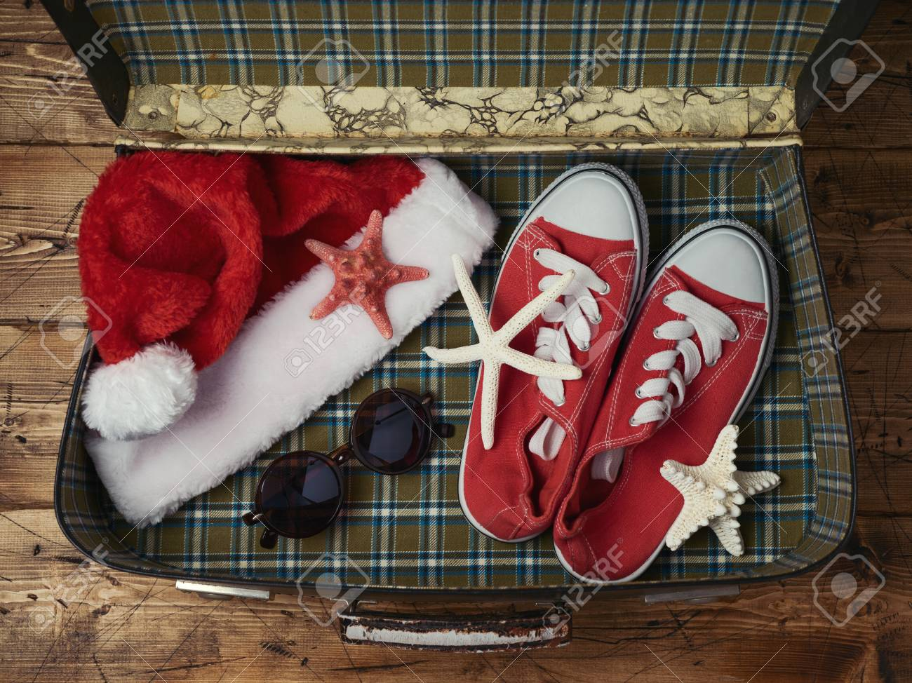 Christmas Sneakers.Christmas Holiday Travel Concept Suitecase With Santa Hat Sneakers