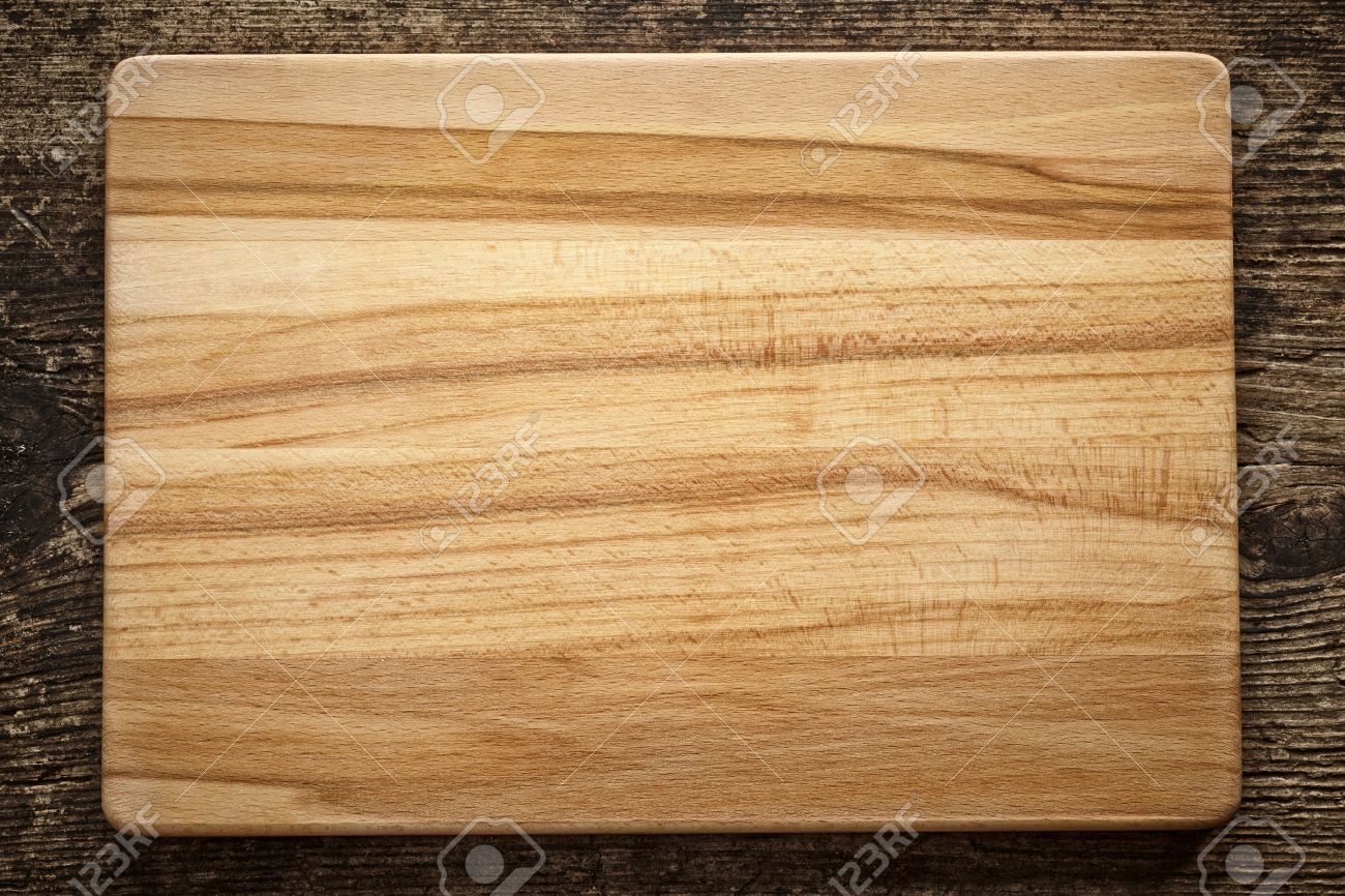 top view of wooden cutting board on old wooden table stock photo