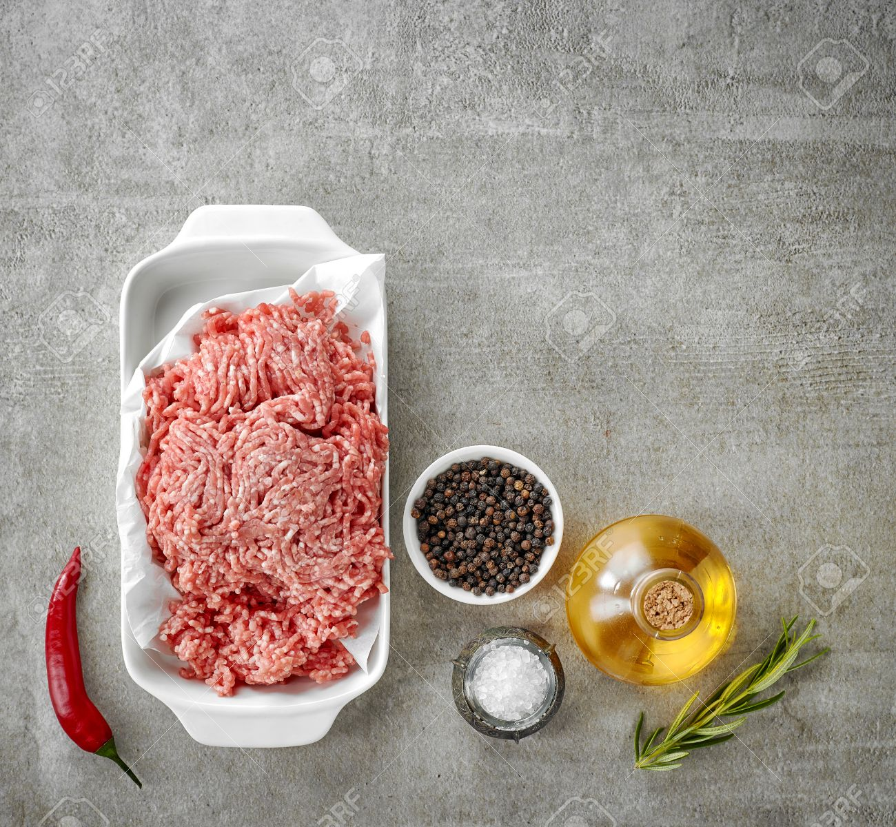 56449991 ground pork and various spices on gray kitchen table top view Stock Photo
