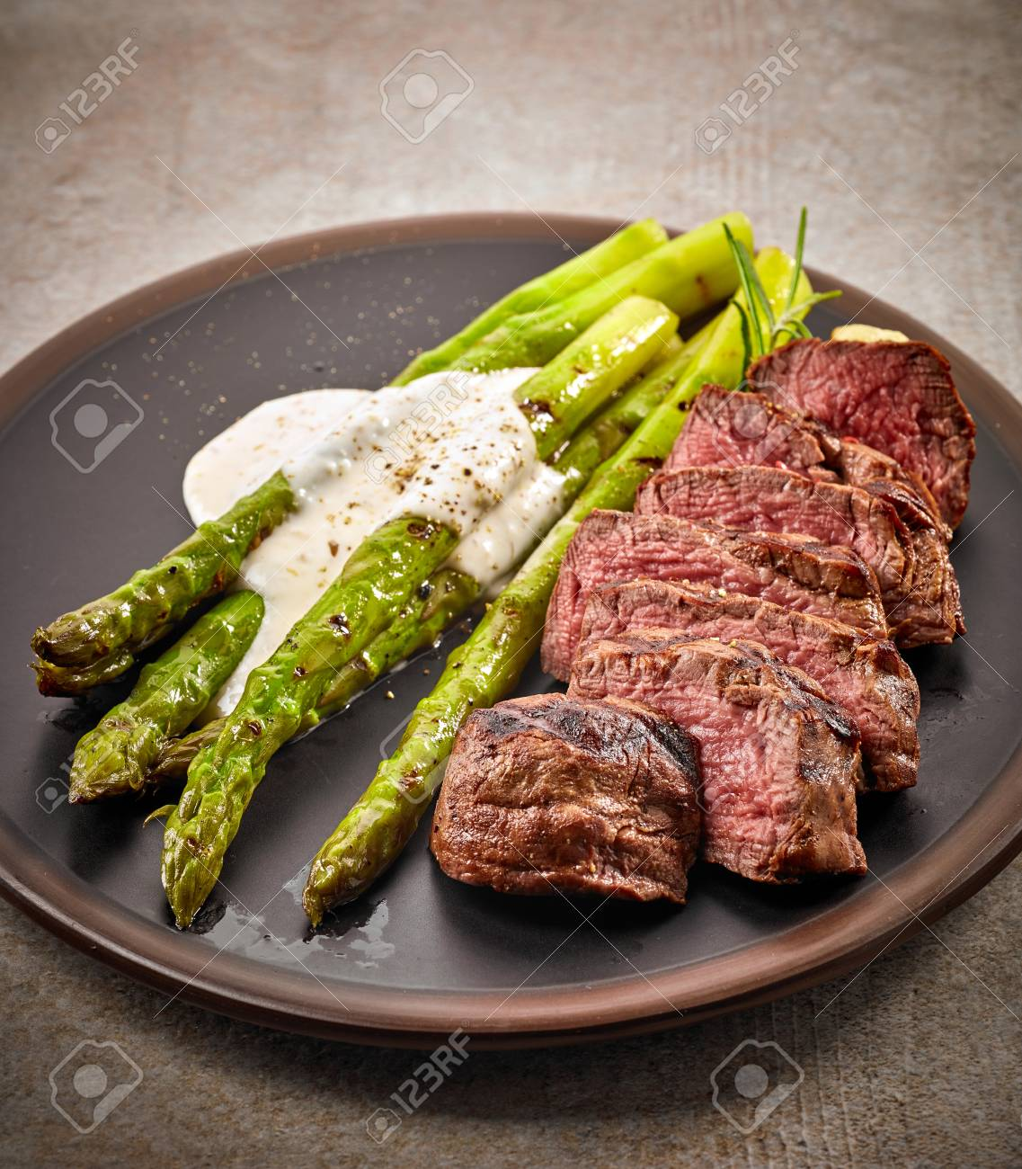 Portion Of Sliced Beef Steak And Asparagus On Dark Plate Stock Photo Picture And Royalty Free Image Image 58394241