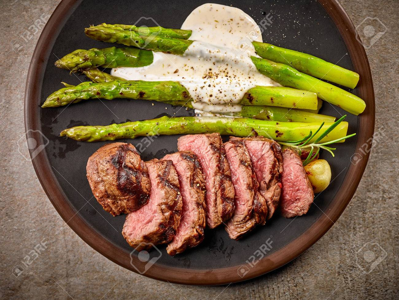 Portion Of Sliced Beef Steak And Asparagus On Dark Plate Top Stock Photo Picture And Royalty Free Image Image 58394246