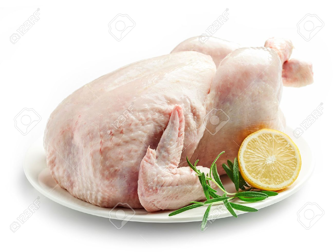 whole raw chicken on plate isolated on white background stock photo