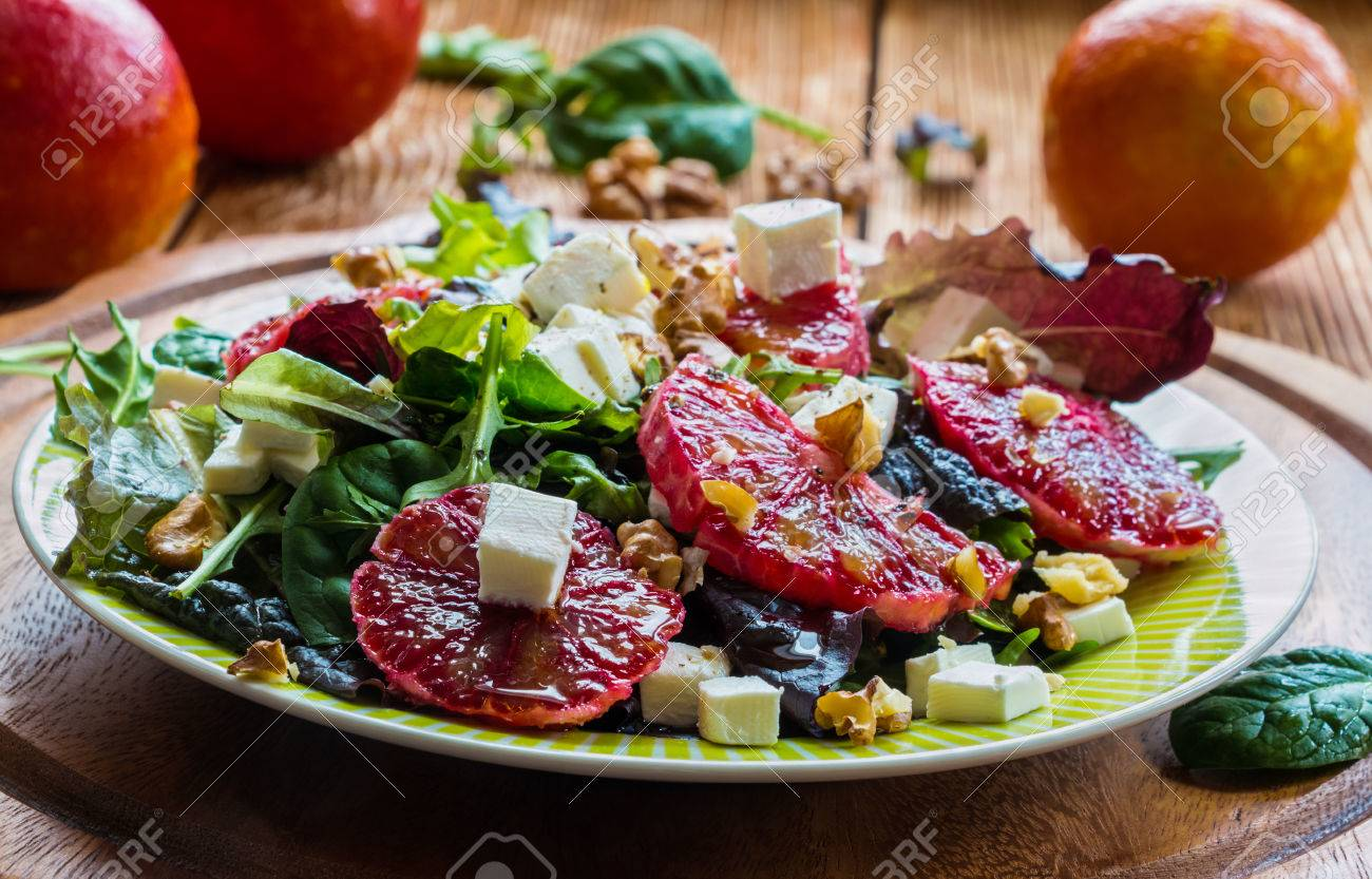 Salad: mix of green salad, feta cheese, red oranges and walnuts. Dressing: olive oil. Selective focus. - 58906807
