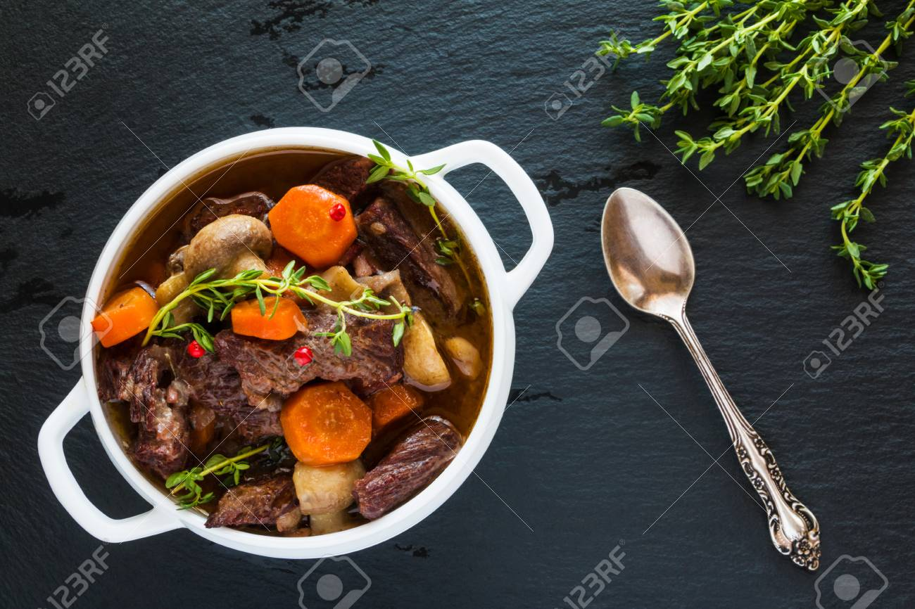 Beef Bourguignon in a white soup bowl on black stone background, top view. Stew with carrots, onions, mushrooms, bacon, garlic and bouquet garni. The dish is served with fresh thyme. - 68287492