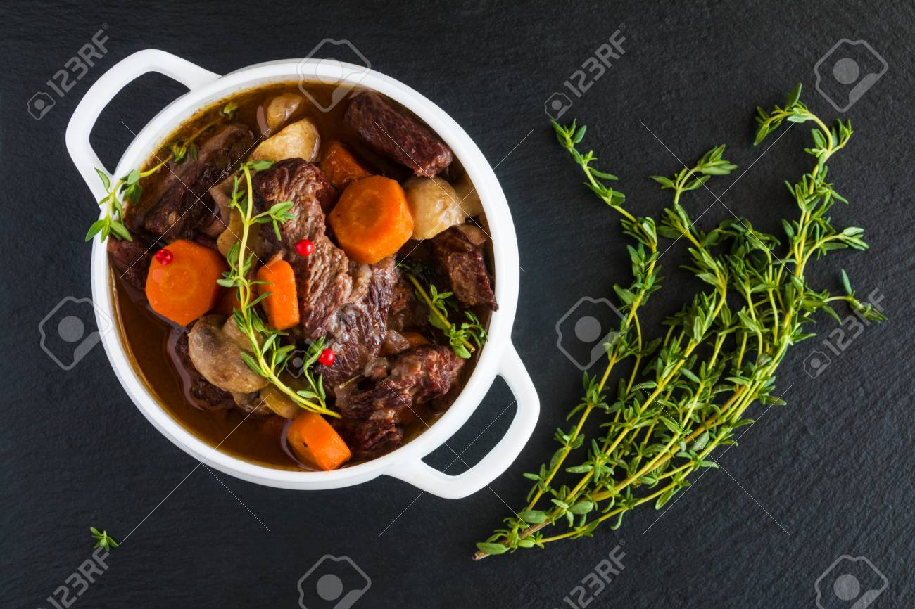Beef Bourguignon in a white soup bowl on black stone background, top view. Stew with carrots, onions, mushrooms, bacon, garlic and bouquet garni. The dish is served with fresh thyme. - 68287505