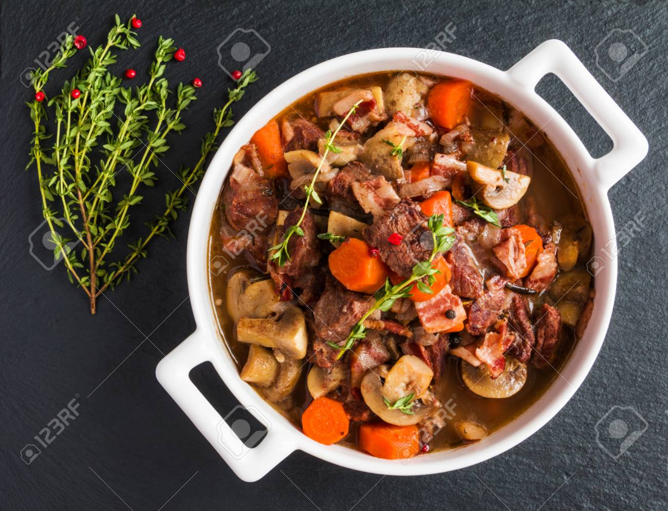 Beef Bourguignon in a casserole on black stone. Stewed with bacon, garlic, carrots, onions, mushrooms, red wine, fresh thyme and spices. Top view. - 66957018