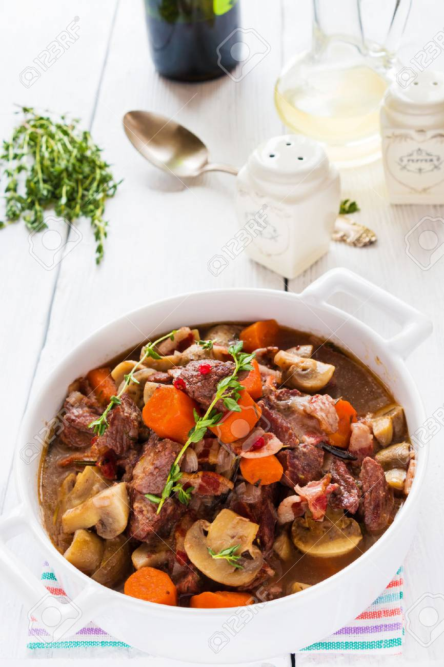 Beef Bourguignon in a casserole on white table. Stewed with bacon, garlic, carrots, onions, mushrooms, and spices. Bunch of fresh thyme, vintage spoon, red wine. - 67098206