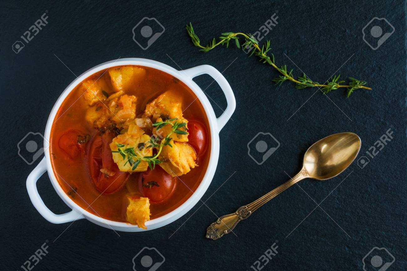 Fish soup with cod, tomato, onion, garlic and thyme in white bowl on black stone background, top view. - 68379394
