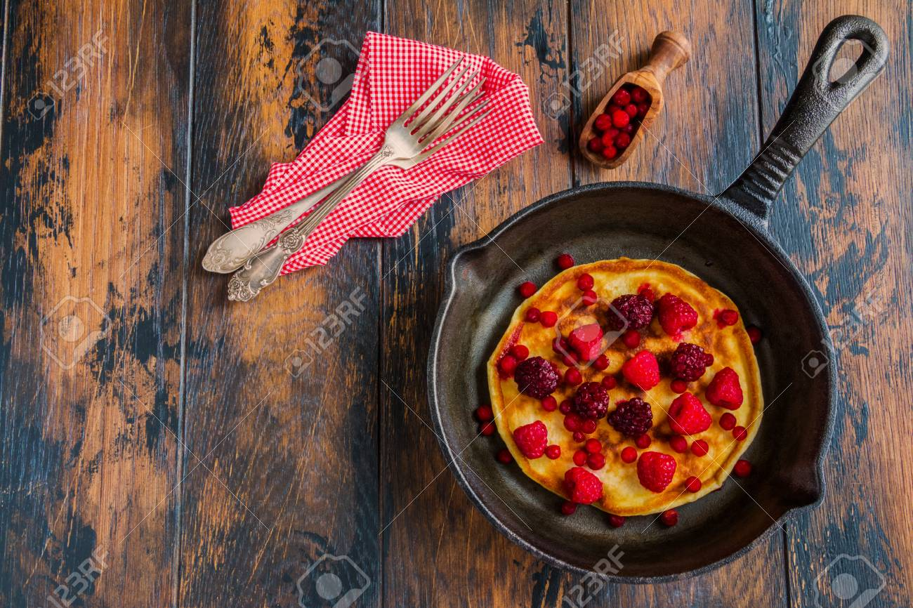 Homemade fried pancakes on a black cast iron skillet. Above are berries, raspberries, cranberries and blackberries. Wooden rustic brown background, top view. - 69794758