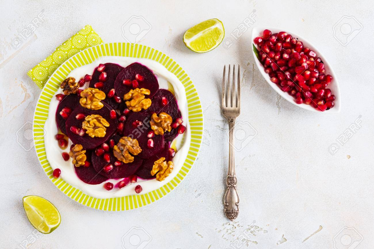 Dietary vegetarian salad of roasted beets with pomegranate seeds, walnuts caramelized in honey and natural yoghurt. Slices of lime, vintage fork, white and gray table, top view. - 69056836