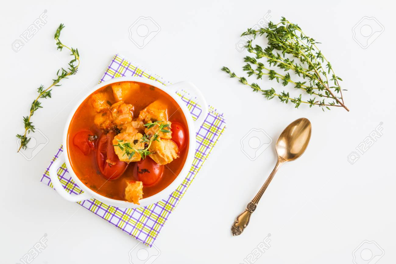 Fish soup with cod, tomato, onion, garlic and thyme in bowl on white table, top view. - 71318589