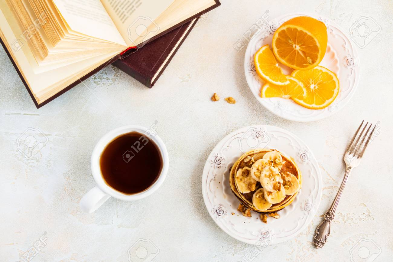 Stack of homemade pancakes with banana, maple syrup and walnuts on vintage plate. Fork, fresh sliced fresh lemon, cup of tea, white and gray concrete background, top view. - 69984576