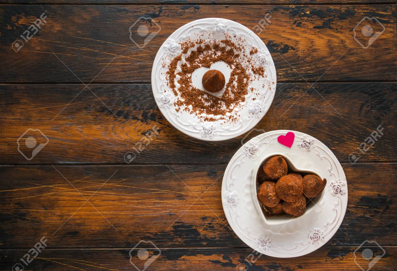 Valentine day, white vintage plates, sweets and hearts made from red paper and grated chocolate. Top view, flat lay, wooden rustic table. - 69986440