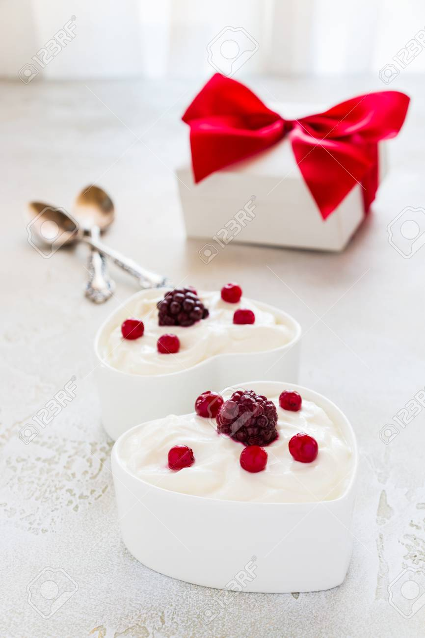 Valentine day decoration, breakfast, yogurt with berries for two in white heart-shaped bowls on the table. - 69914248