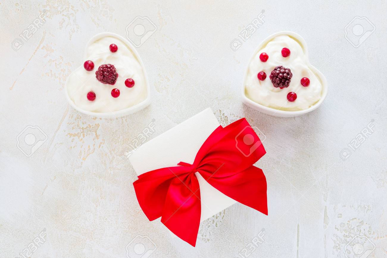Valentine day decoration, breakfast, yogurt with berries for two in white heart-shaped bowls and gift box on the table. Top view, flat lay. - 70095762