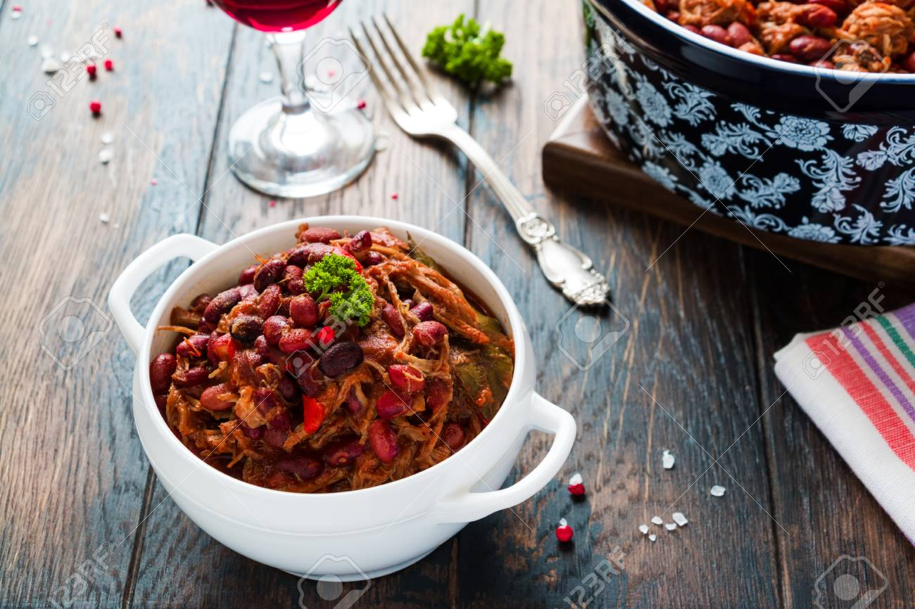 Beans with pork stewed in spicy tomato sauce with onion, paprika, beer, bell and pink pepper. White soup bowl, casserole, glass of red wine and vintage fork on wooden rustic table. - 70588941